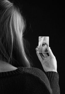 Woman looking into a mirror. Believe in yourself.