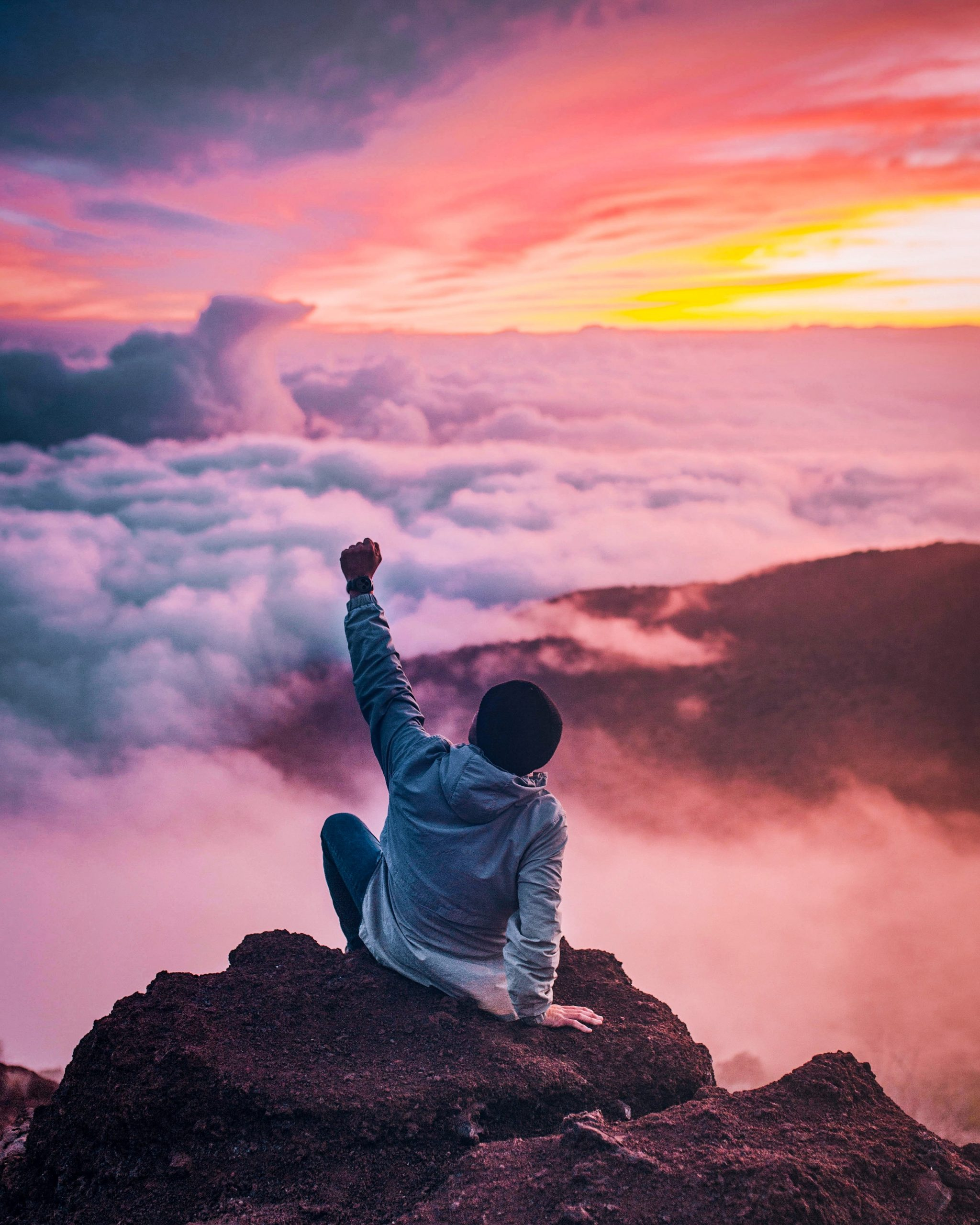 A young man on top of the mountain showing hope for the future after completing anxiety treatment.